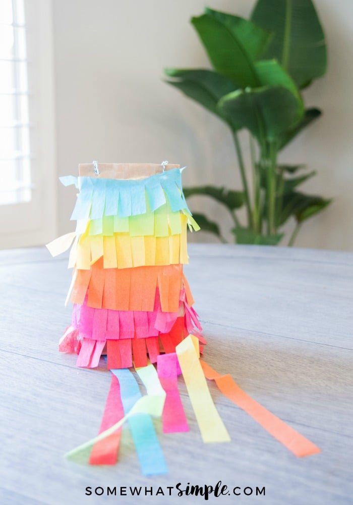 a colorful pinata made out of a paper bag sitting on a wooden table