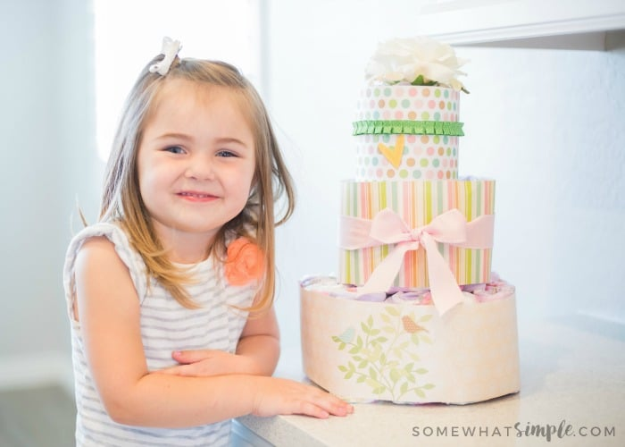 cute little girl next to a diaper cake that will be given as a baby shower gift