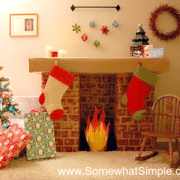 fake fireplace made with cardboard that has stockings hanging from it