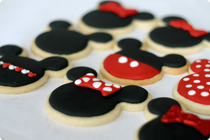 a baking sheet lined with parchment paper filled with DIY mickey mouse and minnie mouse cookies.  The sugar cookies are in the shape of mickey and minnie mouse heads with black icing.  Some have hair bows and others have red pants for Mickey with two white dots.