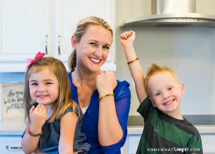 a cute blonde woman with her two children each wearing a colored pasta bracelet