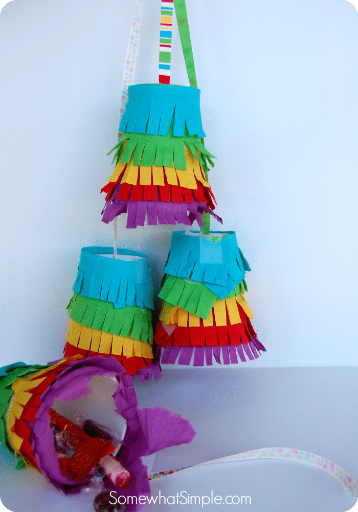 three completed mini pinatas that are made with different colored paper are hanging from above
