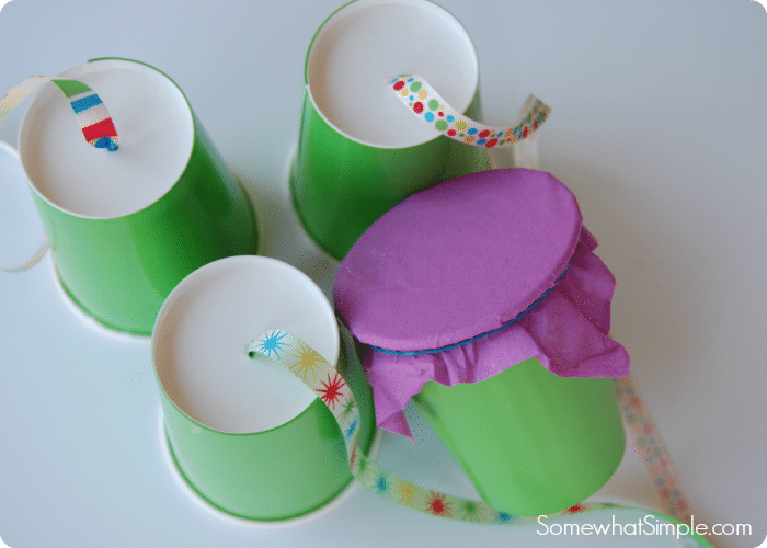 four green cups with ribbon attached to three of them and the fourth has purple tissue paper attached to it with a rubber band. These are the first couple of steps to making a homemade pinata.