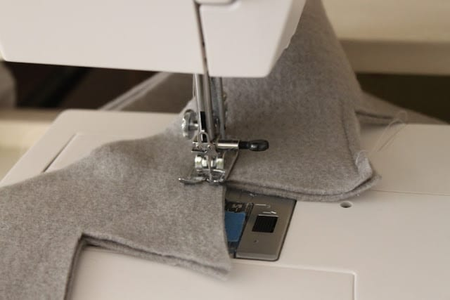 the next step in making a crown with grey felt that was previously cut out of a pattern being sewn on a sewing machine