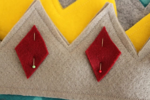 pinning the red felt diamonds to the grey felt crown outline
