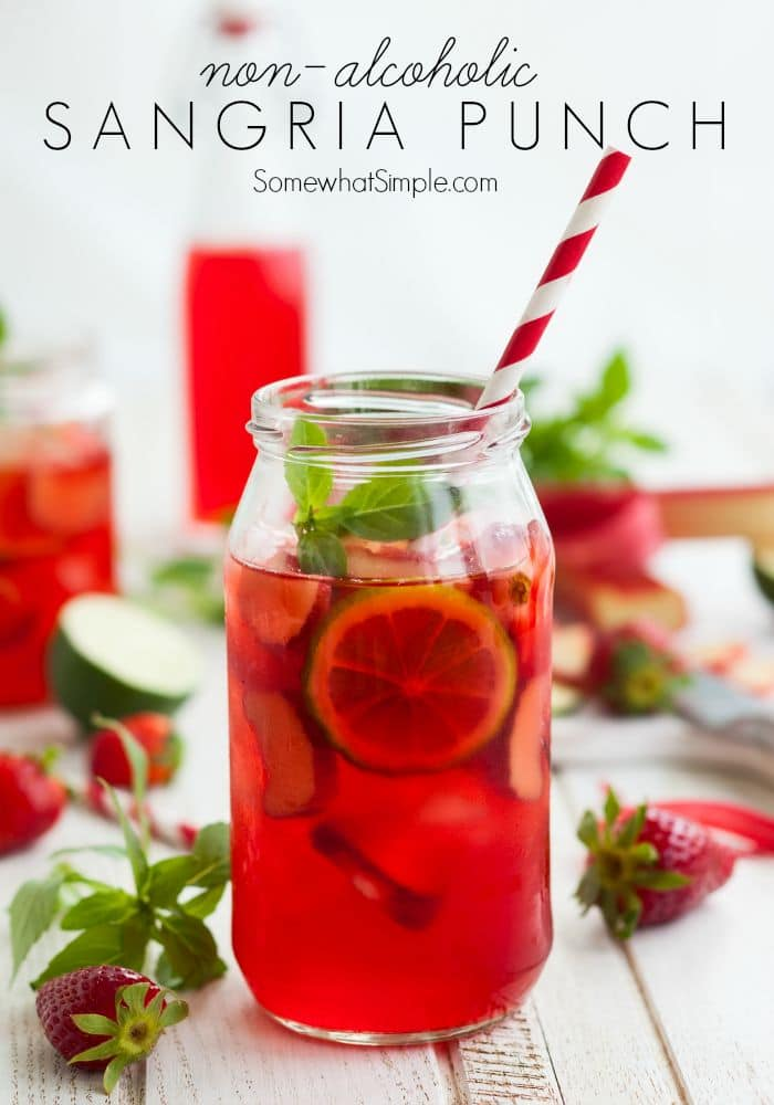 a mason jar filled with this easy Sangria Punch Recipe without alcohol and slices of lime and a striped straw