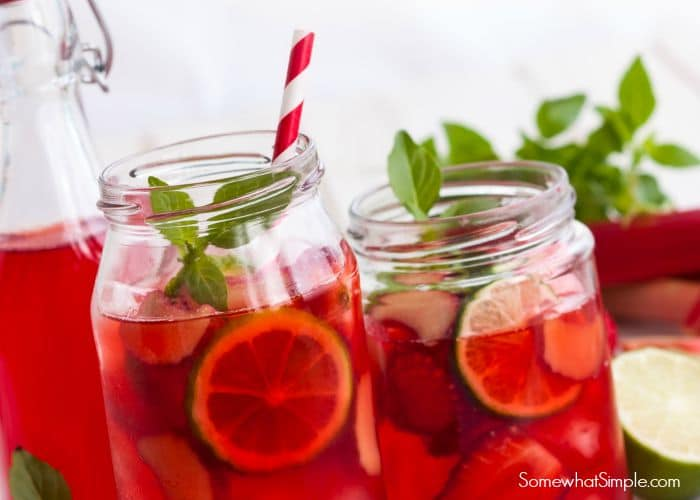 two Mason jars filled with non-alcoholic Sangria Punch Recipe with slices of lime and other fruit, topped with a clover of mint