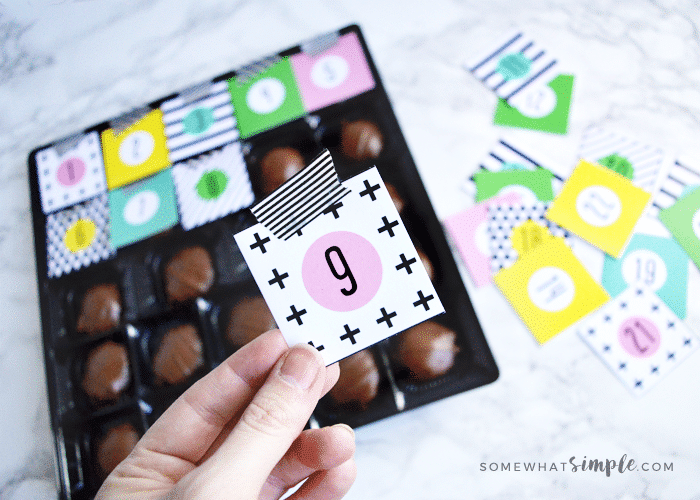 a box of chocolate in the process of becoming a christmas advent calendar using this free printable