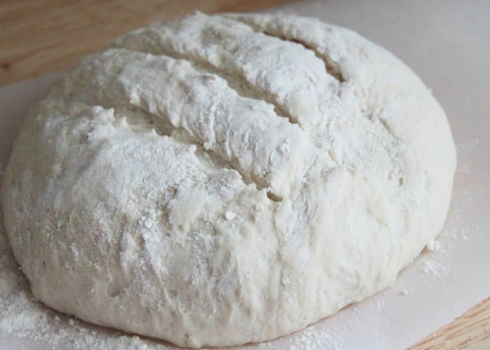 a loaf of uncooked artisan bread on parchment paper with slits cut into the top and flour over the dough