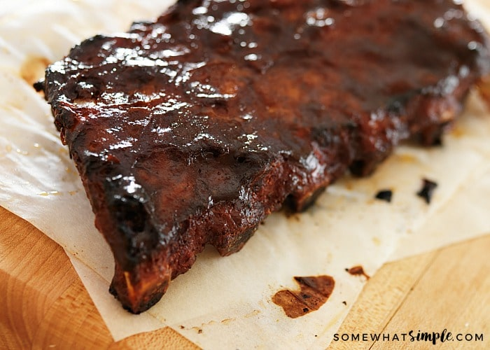 a rack of fall off the bone ribs that were cooked in the oven and covered in bbq sauce laying on a table with parchment paper underneath