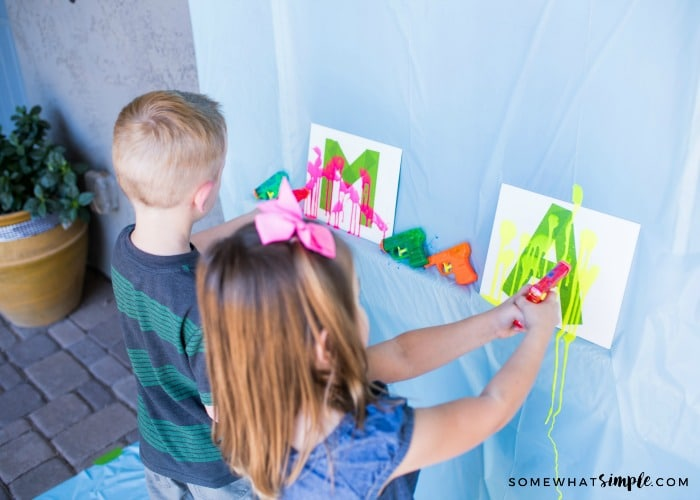 a young boy and girl shooting paint from water guns at a canvas on a wall