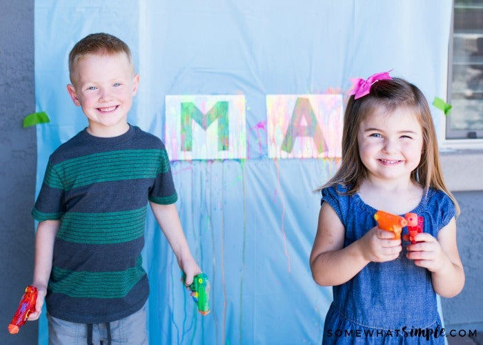 two cute children holding water guns in their hands with a water gun art project set up behind them