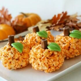 four Orange Halloween popcorn pumpkin balls on a white serving tray