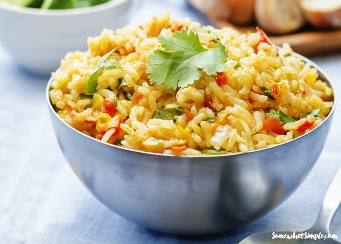 a metal bowl filled with homemade Spanish rice topped with parsley using this simple recipe
