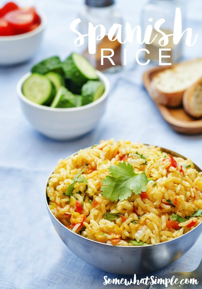 a bowl of Spanish rice made with this easy recipe with a bowl of tomatoes and a bowl of cucumbers in the background