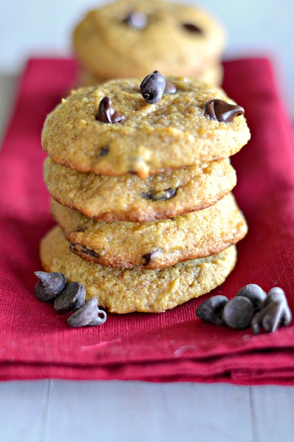 pumpkin chocolate chip cookies stacked on a red napkin