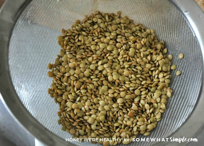 a strainer full of brown lentil beans that are being prepared for crock pot lentil soup