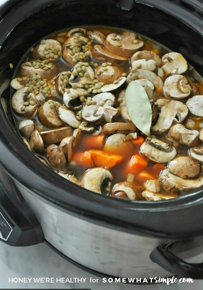 slow cooker filled with broth, mushrooms, lentils and carrots