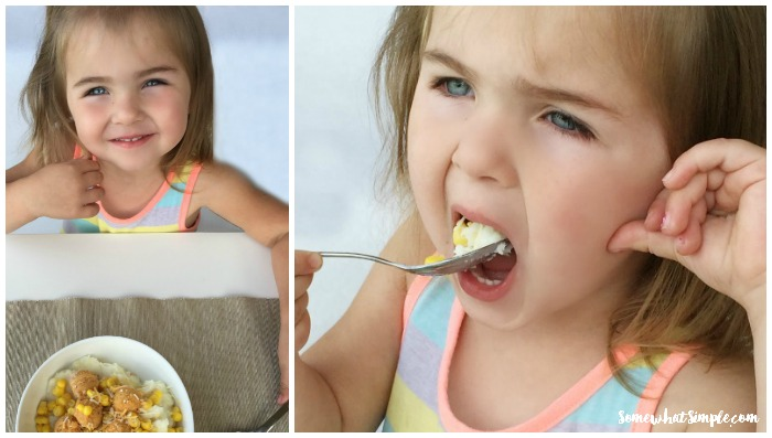 a little girl eating a bite from a chicken and mashed potato bowl