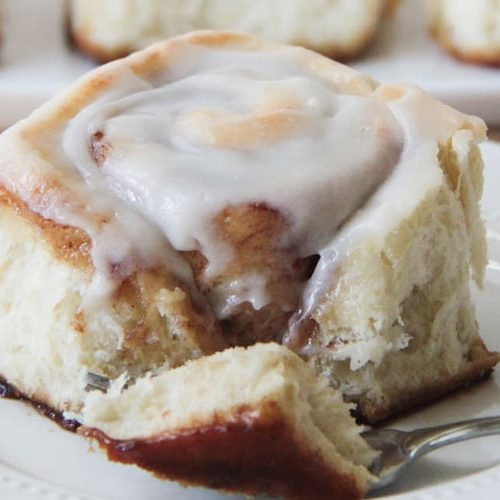 a forking cutting off the corner of a cinnamon roll with a cream cheese frosting on top