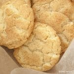 A close up of three soft snickerdoodle cookies topped with cinnamon and sugar with in a container lined with parchment paper