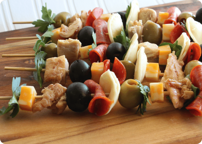 Italian chicken kebobs laying on a wood cutting board is a delicious super bowl snack