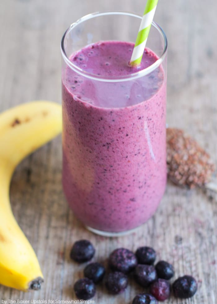 A glass filled with a blueberry pomegranate smoothie with a banana and a spoonful of flax seeds next to the glass on a table.