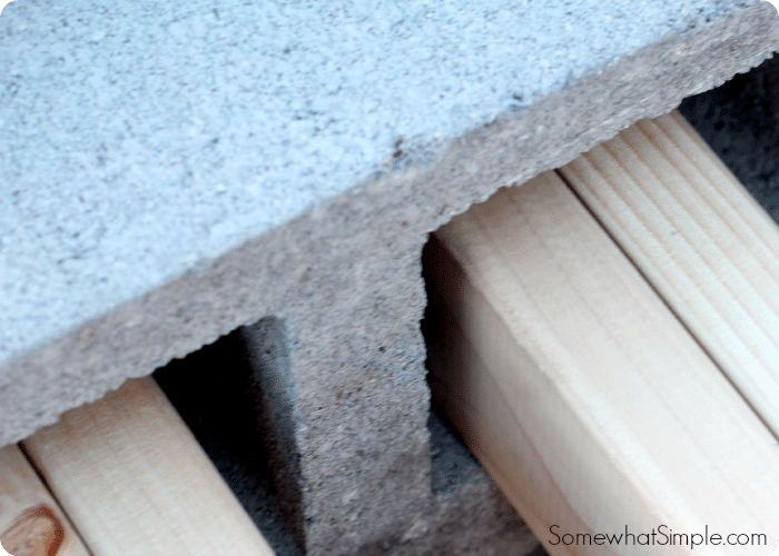 wood planks inserted into cinder blocks is a step when making a cinder block bench