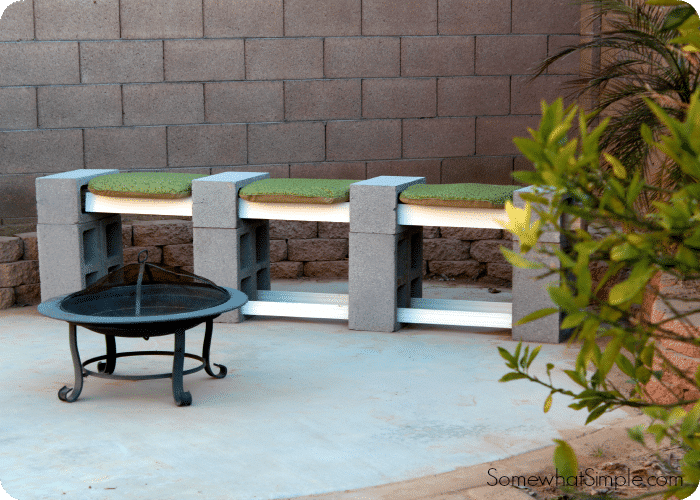 a cinder block bench with cushions on a patio next to a portable fire pit