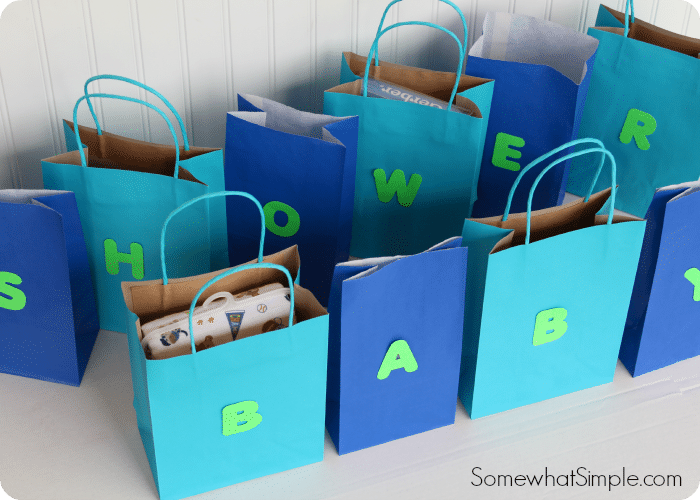 several blue bags with one letter on each bag that spells out baby shower that are used in this easy baby shower game