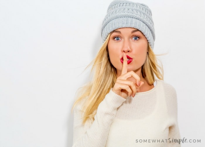 a cute blonde woman with red lipstick wearing a white shirt and grey beanie holding her finger to her lips and mouthing the word shhhh as if she just played an April fools pranks on her husband or boyfriend and is trying to keep it a secret