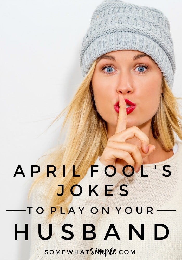a close up of an attractive blonde woman with blue eyes and red lipstick wearing a white shirt and grey beanie holding her finger to her lips and mouthing the word shhhh as if she just played an April fools pranks on her husband or boyfriend and is trying to keep it a secret with the words April fools jokes to play on your husband written at the bottom of the image