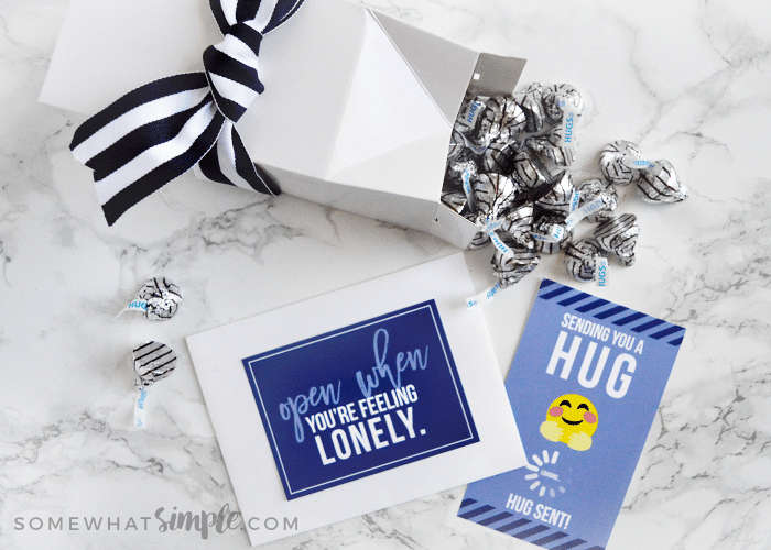 a dark blue card with a white envelope next to a white box laying on its side with Hershey's hugs spilling from the top