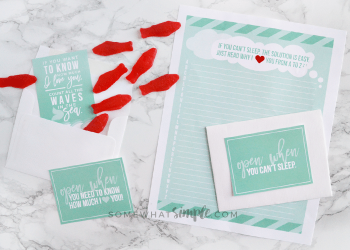a letter with an envelope and several red swedish fish scattered on the counter