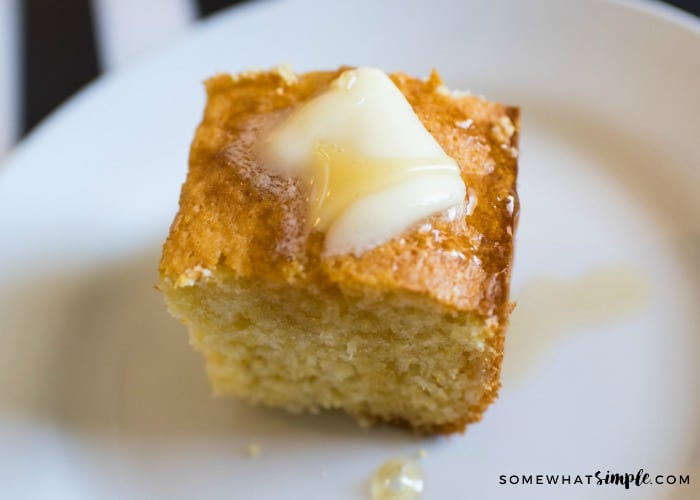 a slice of cornbread made using cake mix on a white plate and topped with a pad of butter