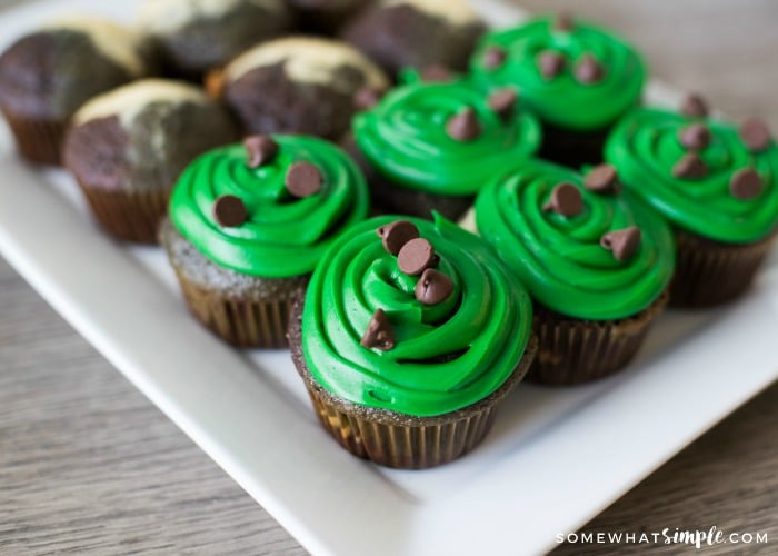 a tray of camo cupcakes on a white tray. half of the army cupcakes are topped with a green frosting and chocolate chips