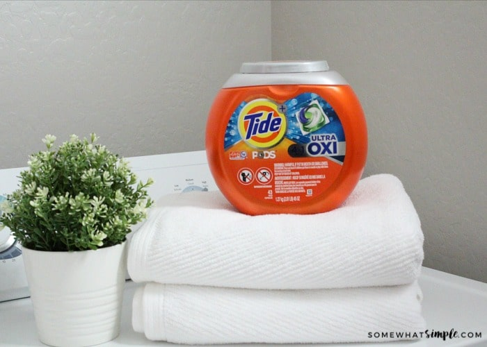 a small stack of white towels on top of a dryer with a container of Tide pods on top