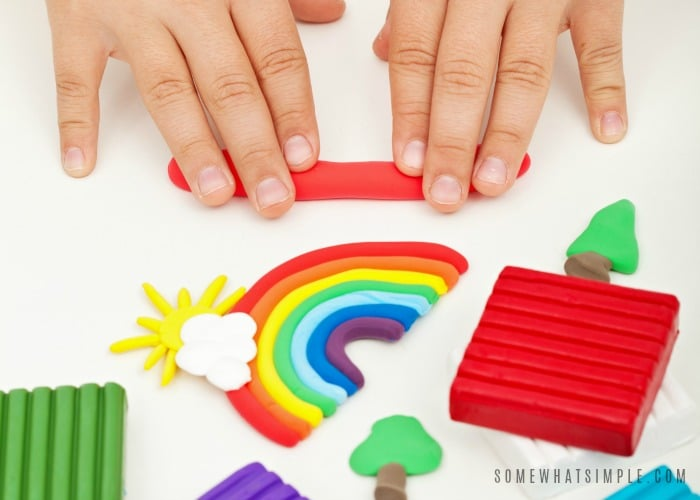 Child hands playing with colorful modeling clay