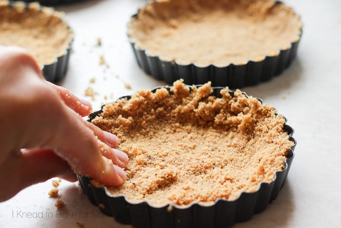pressing a graham cracker crut into a pie tin