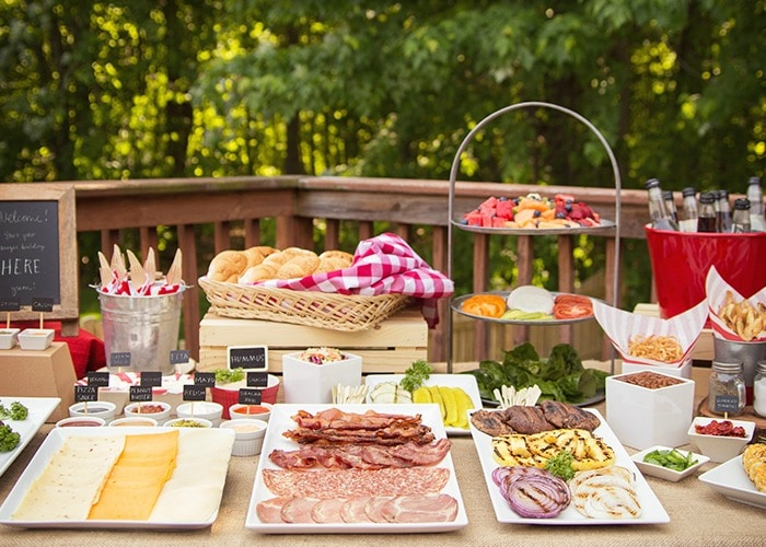 hamburger bar with trays of cheese, meats and vegetables on a picnic table make a perfect setting for a summer bbq