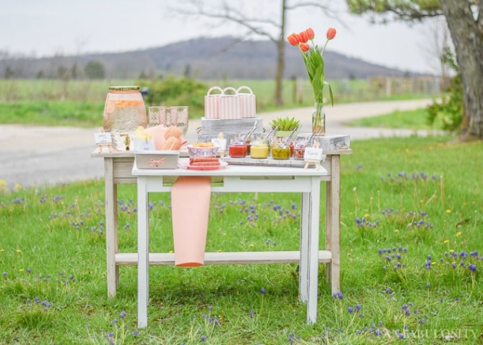 hot dog bar set out on white wood tables on the grass is a fun compliment to a summer bbq