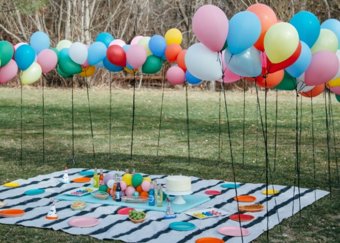 balloons on poles in a park with a picnic blanket on the ground