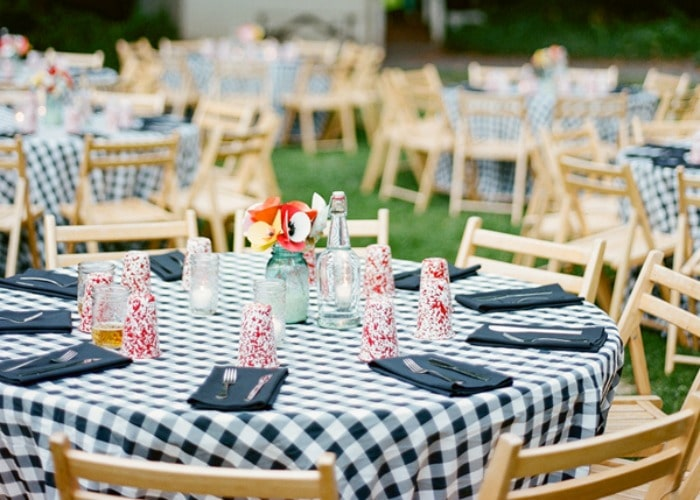 bbq wedding set up using black and white checkered table cloths and light wood chairs