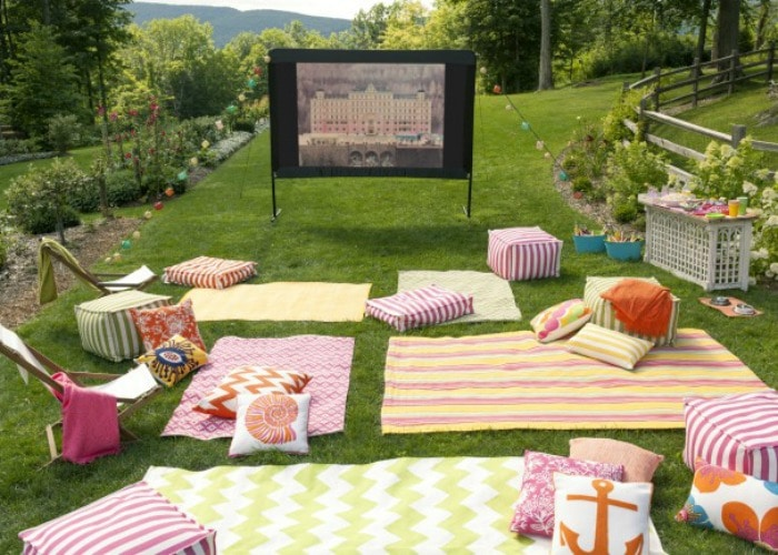 outdoor movie night with blankets and pillows laid on the grass is a fun bbq activity