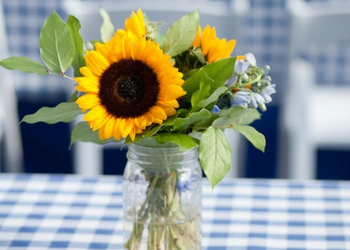 bbq party table setting with sunflowers in a mason jar