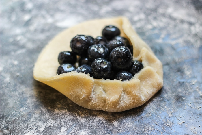 a flat piece of pastry dough being folded up around a pile of blueberries