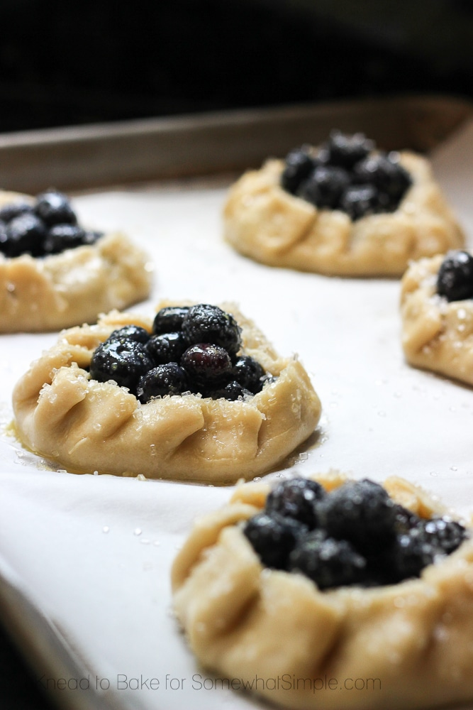 several uncooked Blueberry Galettes on a baking sheet getting ready to go into the oven