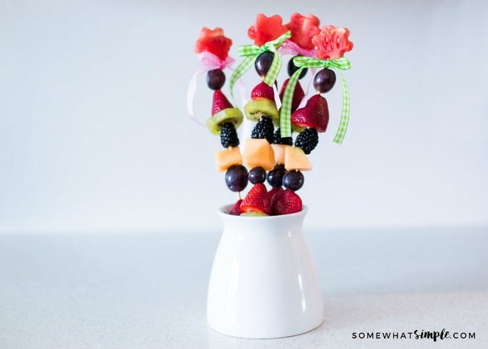 a tall white dish filled with fruit kabobs made with watermelon, grapes, strawberries and other delicious fruit