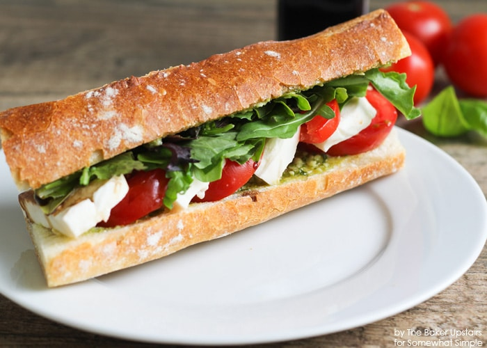a Caprese Sandwich on a white plate filled with lettuce, tomatoes, mozzarella cheese and pesto made using this easy Recipe
