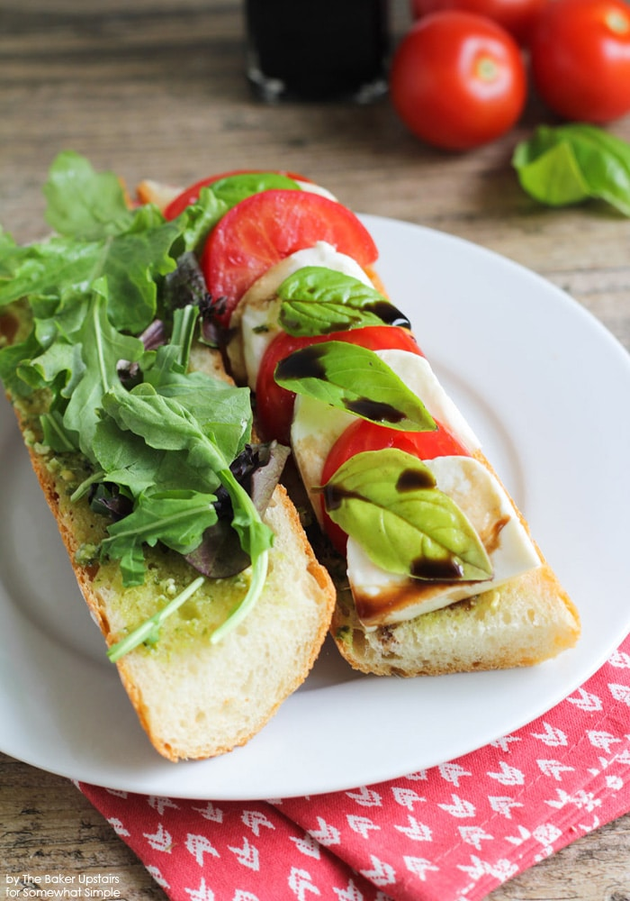 two halves of a Caprese Sandwich on a white plate using this Recipe.  One side has lettuce and pesto and the other side has basil, balsamic, tomatoes and mozzarella cheese.